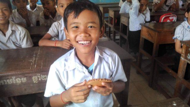 NOM POPOKのお菓子を食べるカンボジアの小学生